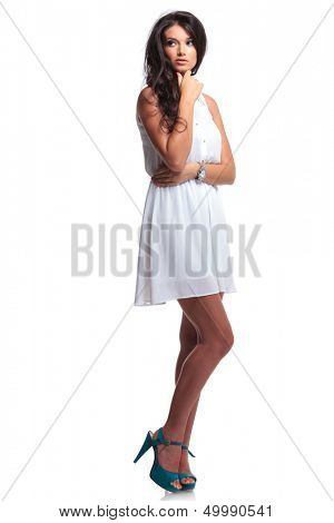 full length picture of a young beautiful woman touching her chin and looking away from the camera. isolated on a white background