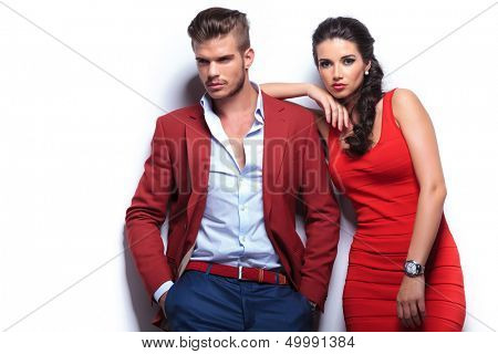 young fashion man and woman against white wall, posing for the camera