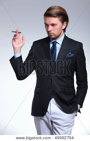 young sylish business man holding a cigarette and a hand in his pocket while looking down, away from the camera. on a gray background
