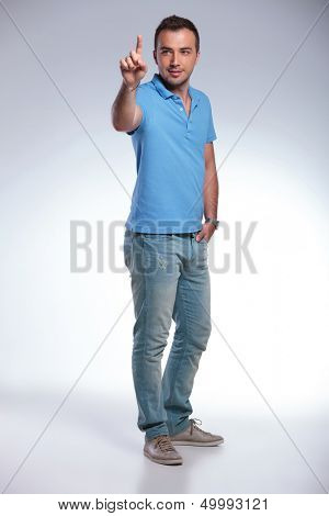 full length photo of a young casual man pushing an imaginary button while looking at it and holding a hand in his pocket. on gray background