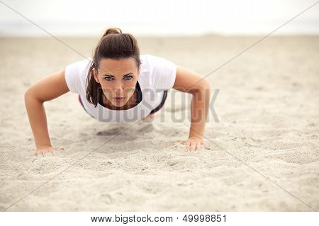 Athletic Woman Doing Push Up On The Beach