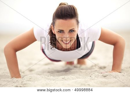 Happy fitness caucasian woman on the beach smiling while doing push up exercise. Active and healthy lifestyle. poster