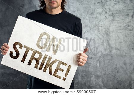 Man holding banner with ON STRIKE printed protest message. poster