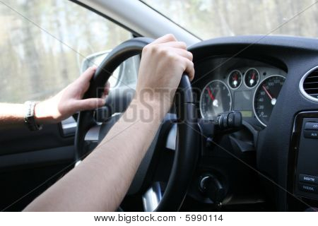 Driver Man Holds A Steering Wheel Of  His Car