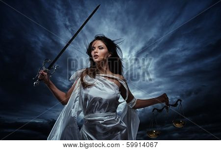 Femida, Goddess of Justice, with scales and sword against dramatic stormy sky