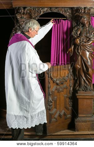Priest in white surplice entering the confession booth of a 17th century medieval church