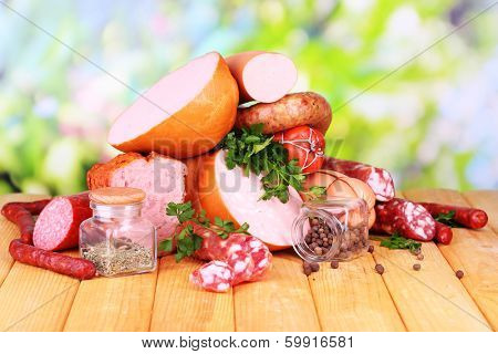 Lot of different sausages on wooden table on natural background poster