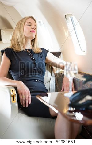 Beautiful rich woman with eyes closed relaxing in private jet