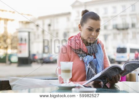 Young woman reading book at sidewalk cafe
