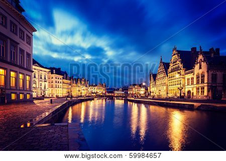 Vintage retro hipster style image of travel Europe Belgium background - Ghent canal, Graslei and Korenlei streets in twlight the evening. Ghent, Belgium