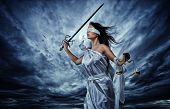 Femida, Goddess of Justice, with scales and sword wearing blindfold against dramatic stormy sky poster