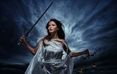 Femida, Goddess of Justice, with scales and sword against dramatic stormy sky poster