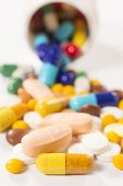 Bunch of pills on white background.Selective focus on the front yellow pill poster