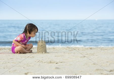 Little Girl Blowing On Cake Made With Sand