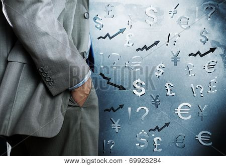 Bottom view of businessman and currency signs at background poster