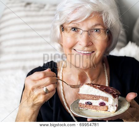 Senior lady looking happy at camera, she likes to eat a piece of cream cake