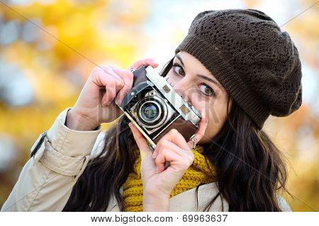 Fashionable Woman Taking Photo In Autumn With Retro Camera