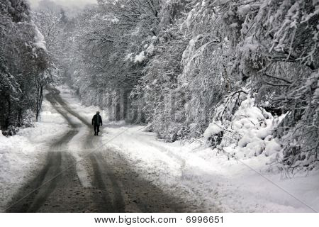A man walking down a snow covered road