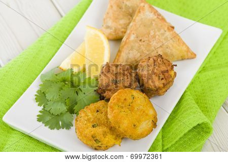 South Asian Starter Selection - Aloo Tikki, Onion Bhaji and Vegetable Samosas, served with lemon wedges. poster