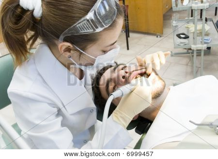 woman dentist treats a patient's teeth