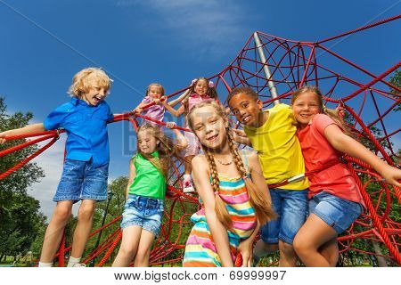 Many kids stand on red ropes together in park