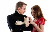 The happy young couple with a small amusing kitten on a white background. poster