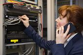 Pretty computer technician talking on phone while fixing server in large data center poster