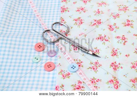 Sewing tools in a vintage fabric background with scissors and buttons