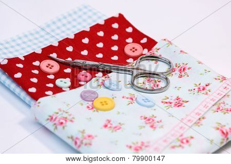 Sewing tools with various vintage fabric background with scissors and buttons