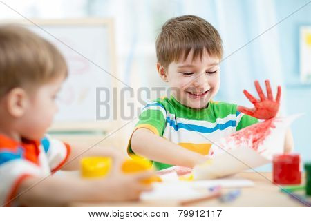 smiling kids playing and painting
