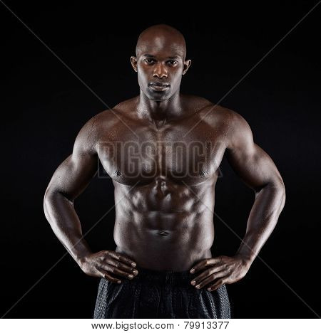 Portrait of a strong afro-american man showing off his physique against black background. Shirtless male model with his hands on hips. poster