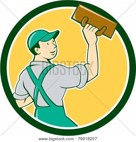 Illustration of a plasterer masonry tradesman construction worker standing with trowel looking to the side viewed from rear set inside circle on isolated background done in cartoon style. poster