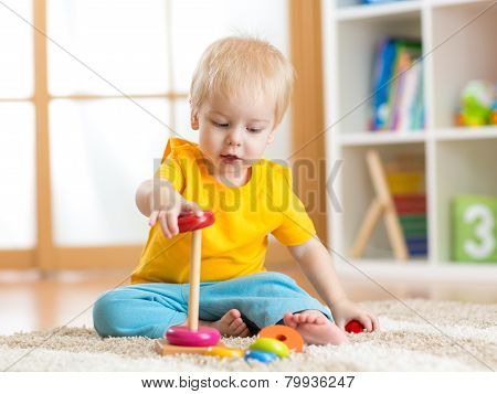 cute child playing with color toy indoor poster