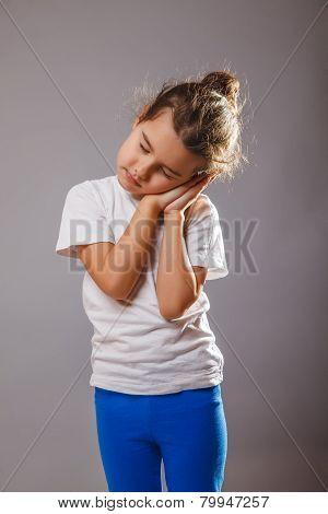 baby girl sleeping lunatic standing hand under his cheek on a gr