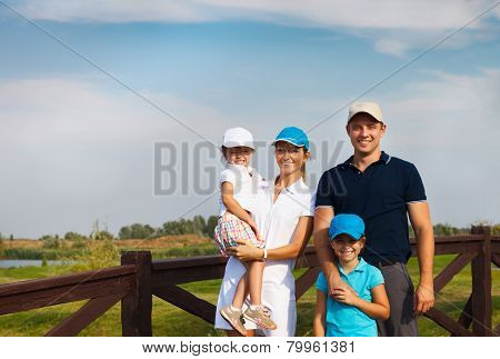 Happy Young Family In Golf Country Club