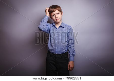 boy shirt ponders over gray background