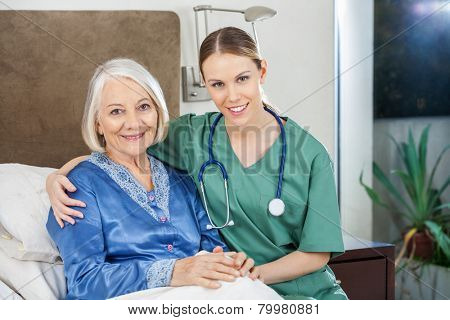 Portrait of happy female caretaker with arm around senior woman at nursing home