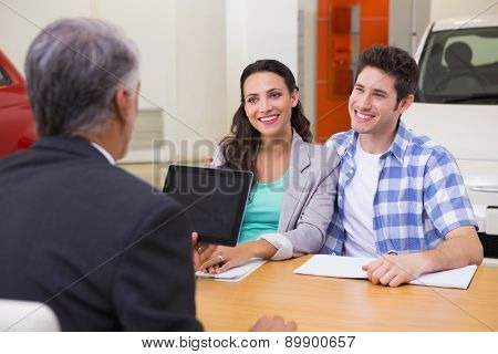 Smiling couple talking with a car dealer at new car showroom