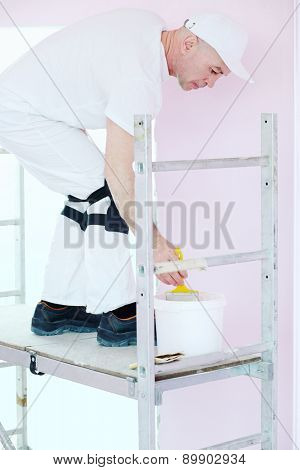 Construction finisher in white clothes with brush and paint stands on scaffolding