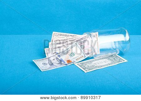 Dollar Bills Woken From A Glass Jar Near A Dollar, Side View, Blue Background