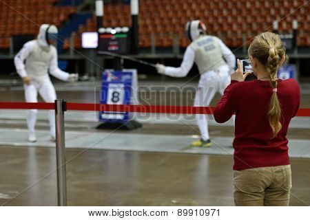 ST. PETERSBURG, RUSSIA - MAY 3, 2015: A girl makes a photo of Russian fencers training during the International fencing tournament St. Petersburg Foil, The tournament is the stage of FIE World Cup