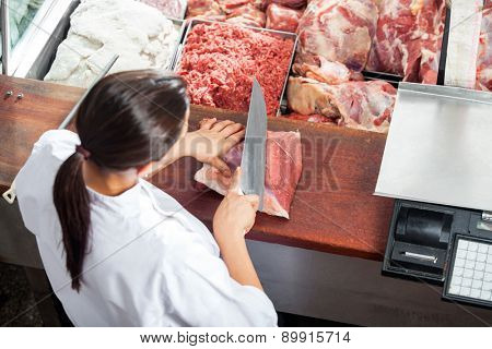High angle rear view of female butcher cutting red meat at butchery