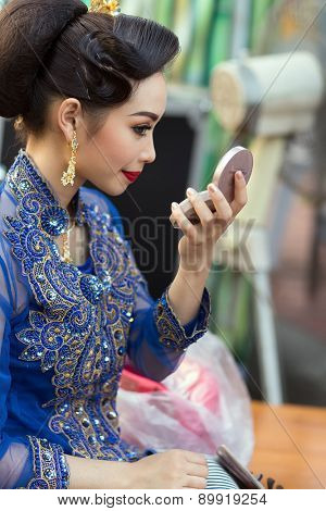 BANGKOK, THAILAND, February 17, 2015: A Thai lady dancer is checking her makeup on a mirror before the show celebrating the new Krung Kasem floating market in the Thewet district of Bangkok, Thailand