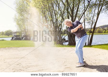 Senior golfer swinging golf club in sand bunker.