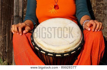 Young Lady Drummer With Her Djembe Drum On Rustic Wooden Door Background