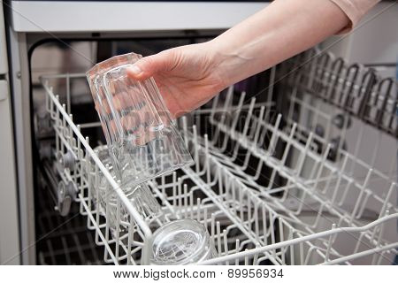 Woman Putting Glass In The Dishwasher