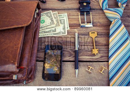 Men accessories: tie, cufflinks, dollars, strap, pen, mobile phone, document bag and key on the old
