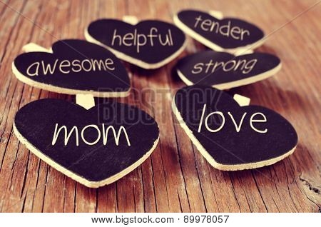 some heart-shaped blackboards with concepts referring to a good mom written in them, such as love, helpful, awesome, tender or strong, placed on a rustic wooden surface poster