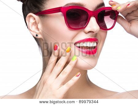 Beautiful girl in pink sunglasses with bright makeup and colorful nails. Beauty face.