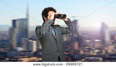 Businessman in search for opportunities on the top of a skyscraper